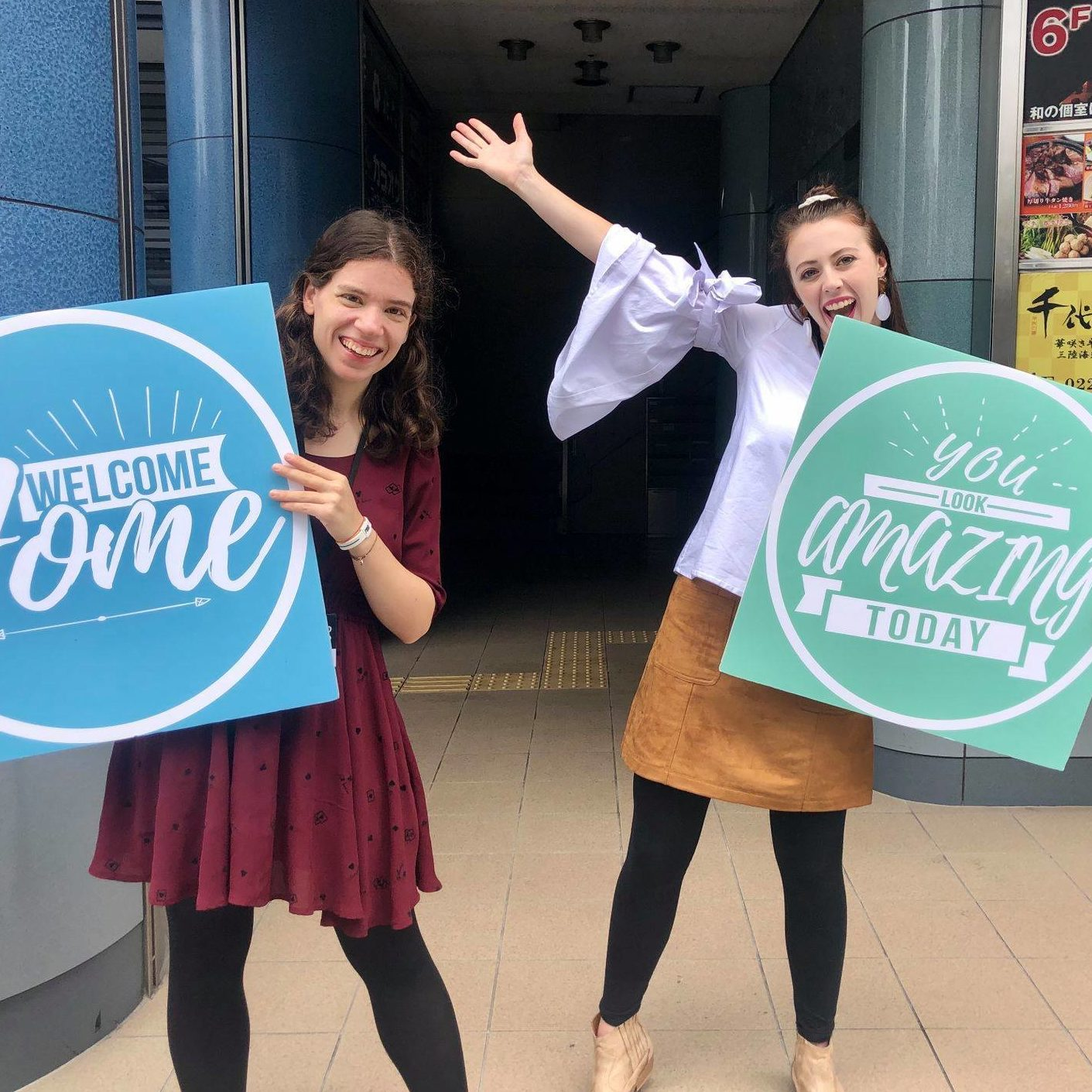 Lifehouse Sendai, two girls smiling and welcoming people with bright signs